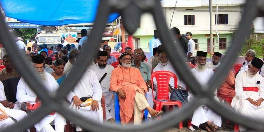 Orthodox faction awaits in front of the gates to enter the church at Piravom on Wednesday.