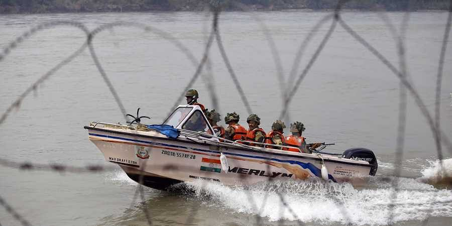 BSF soldiers patrol on a boat in river Chenab at Pargwal area along the India Pakistan border in Jammu district.
