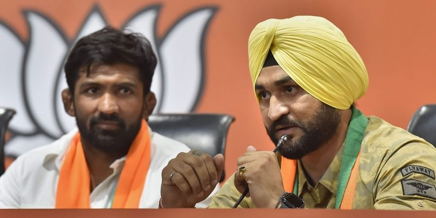 Former Indian hockey captain Sandeep Singh and Olympic medallist wrestler Yogeshwar Dutt talk to the media after joining BJP in New Delhi..