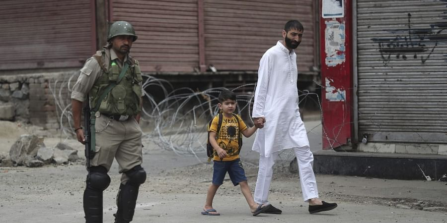 In this Friday, Aug. 30, 2019, file photo, a man walks with a child past an Indian paramilitary soldier standing guard during restrictions ahead of Friday prayers in Srinagar. | (File | AP)