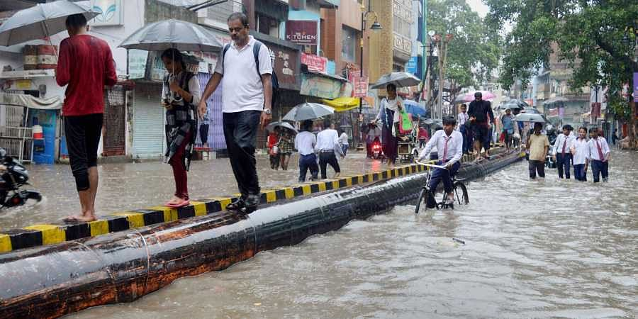Pedestrians walk through a waterlogged road following heavy rainfall in Varanasi Friday.