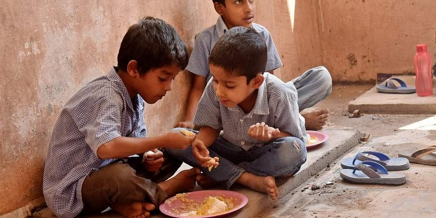 School children share mid day meal.