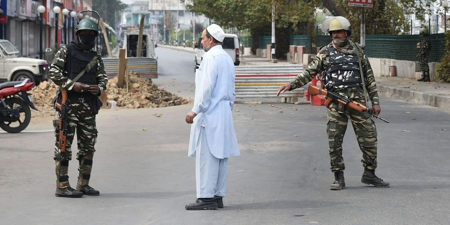 Security personnel stand guard on a road leading to Lal Chowk during restrictions in Srinagar Friday Sept. 27 2019. | (Photo | PTI)