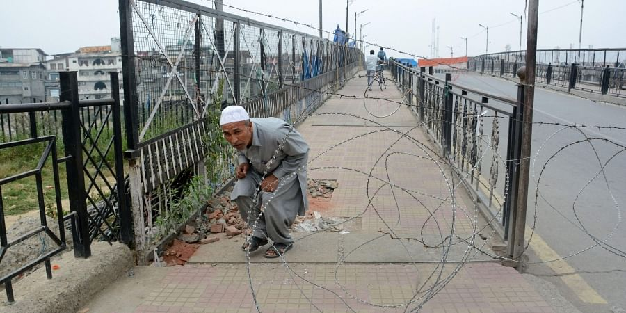 An elderly man attempts to cross through a blockade during restrictions after the abrogration of Article 370 and bifurcation of State in Srinagar.
