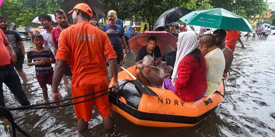 Nation Disaster Response Force NDRF workers rescue an elderly patient from flood-affected area of Bahadurpur following heavy monsoon rainfall in Patna Sunday
