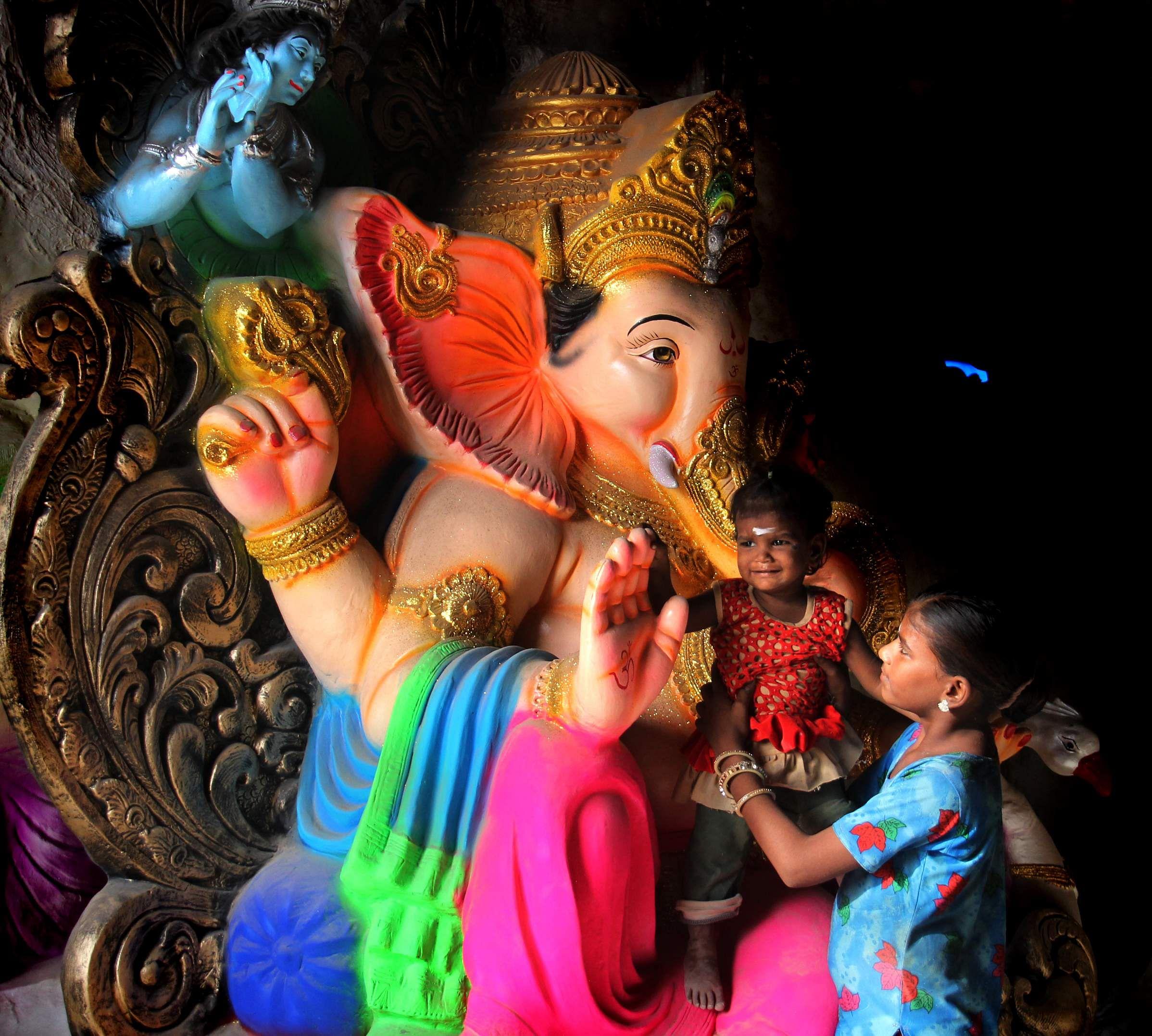 A small girl is made to sit on the lap of a Lord Ganesh statue during Vinayagar Chaturthi at Madurai. (Photo | EPS/k.k.sundar)