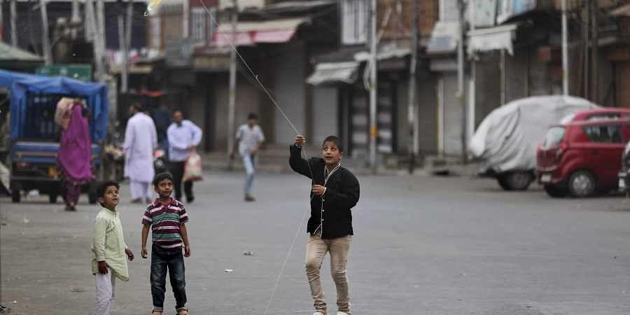 In this Tuesday, Sept. 17, 2019, photo, a Kashmiri child flies a kite outside his home in Srinagar.   (Photo   AP)