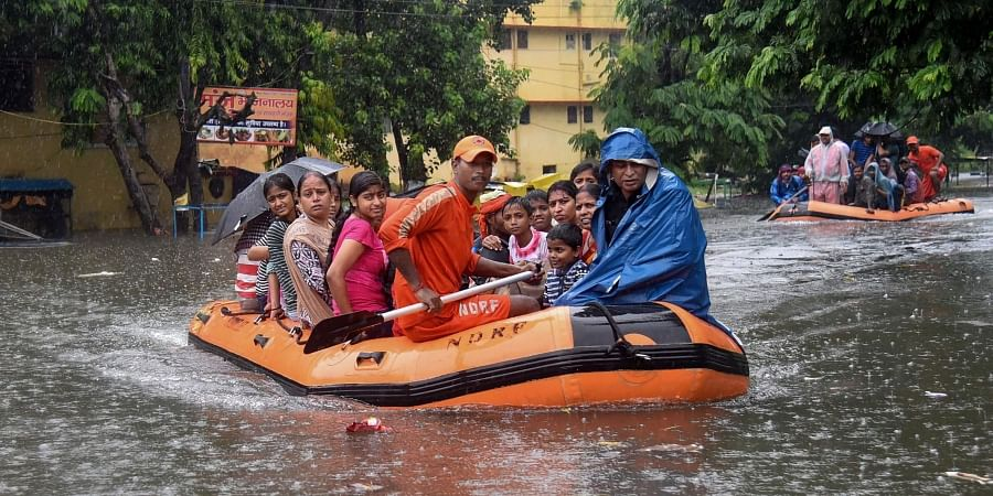 State Disaster Response Force SDRF workers rescue people from flood-affected area of Bahadurpur following heavy monsoon rainfall in Patna. (Photo | PTI)