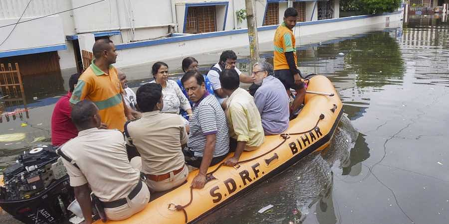 Bihar Deputy CM Sushil Kumar Modi (extreme right in grey shirt) and his family members being rescued by a SDRF team from his flooded residence at Rajendra Nagar in Patna on Monday.