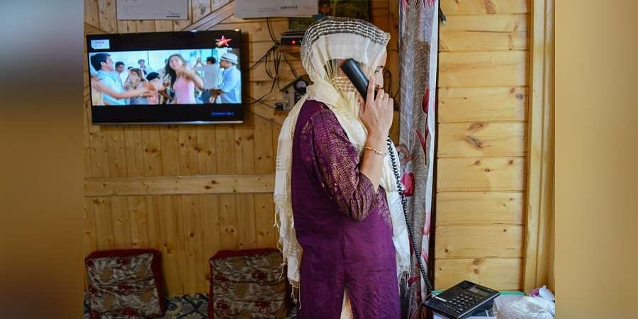 A resident talks on the phone after the authorities on Thursday restored 19 more telephone exchanges in Kashmir a month after the services were snapped