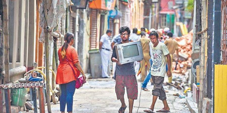 Residents of Bowbazar area evacuate with their belongings, on Friday.