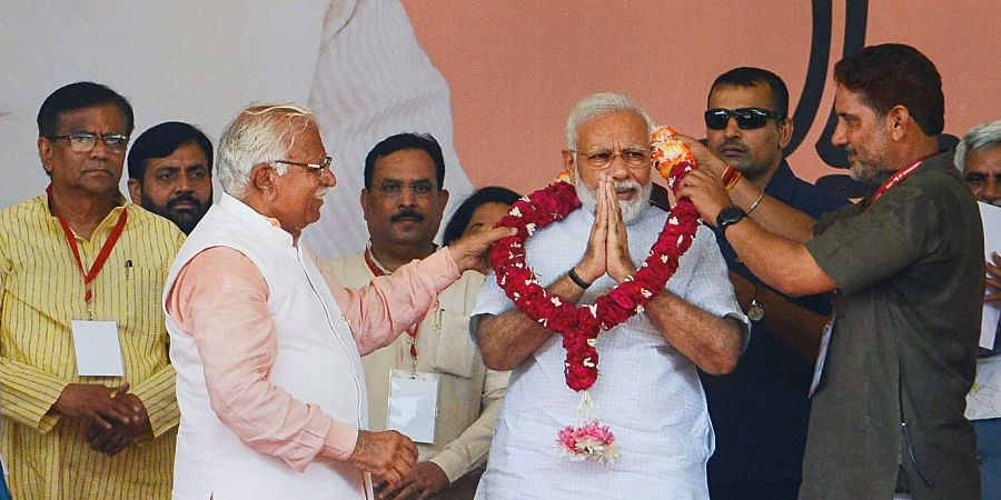 Prime Minister Narendra Modi with Haryana Chief Minister Manohar Lal waves at the crowd during a public rally in Rohtak Sunday September 8 2019. | PTI