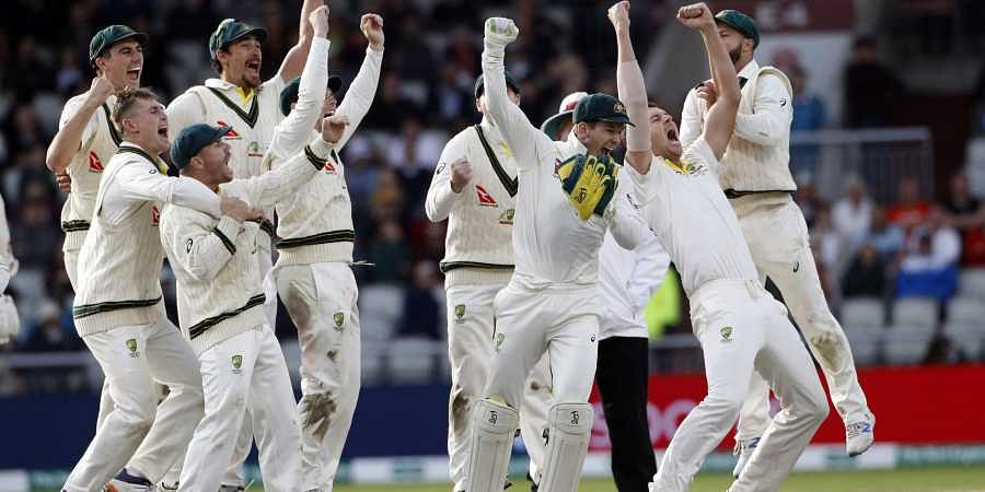 Australia players celebrate after winning the fourth test and retaining the Ashes during day five of the fourth Ashes Test cricket match between England and Australia at Old Trafford in Manchester, England, Sunday Sept. 8, 2019. | AP