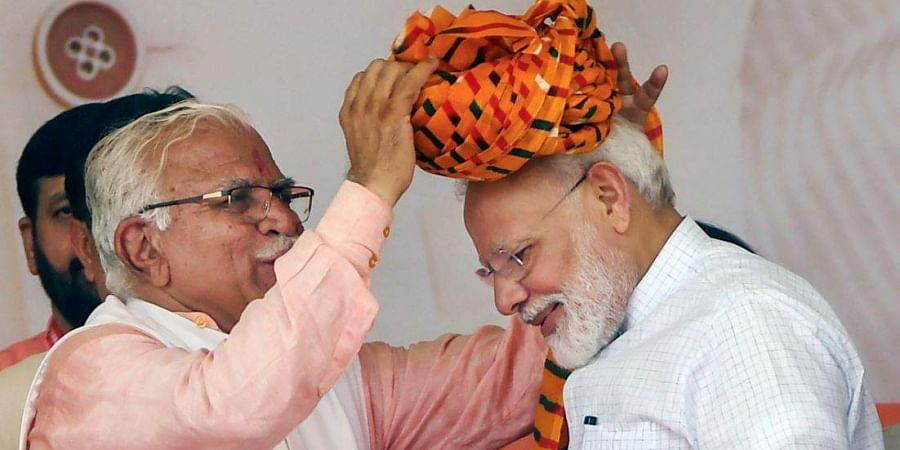 Prime Minister Narendra Modi is presented a turban by Haryana Chief Minister Manohar Lal Khattar during a public rally in Rohtak on September 8, 2019.