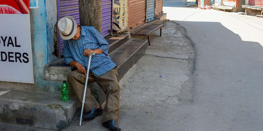 An elderly man takes a nap at a closed market during restrictions after the abrogration of Article of 370 and bifurcation of state in Srinagar Monday September 9 2019. | PTI