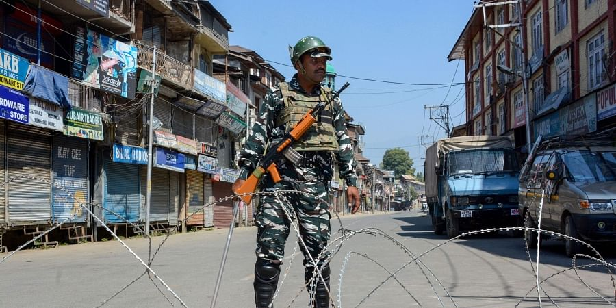 A security person stands guard at a blocked road during restrictions after the abrogration of Article of 370 and bifurcation of state in Srinagar Monday September 9 2019. | PTI