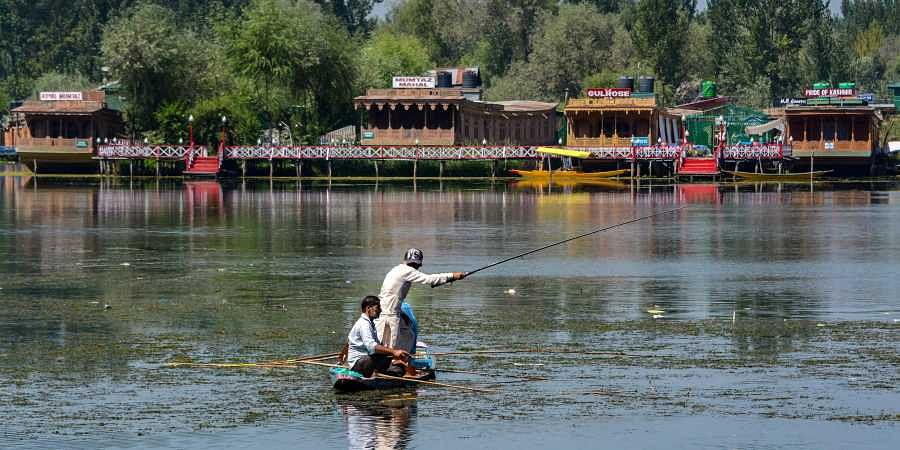 Residents fish on a deserted Dal lake during restrictions after the abrogration of Article of 370 and bifurcation of state in Srinagar Monday September 9 2019. | PTI