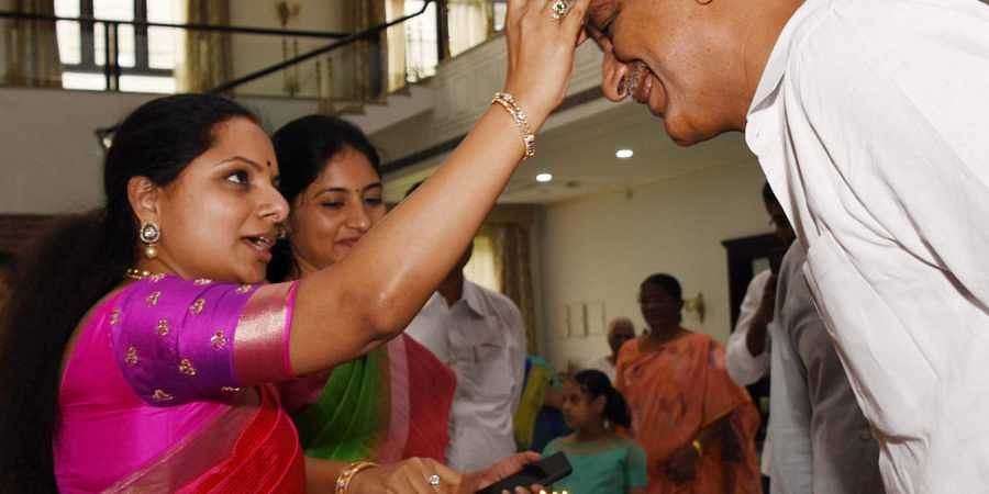 T Harish Rao being welcomed with tilak by Kavitha at thier house after swron in as cabinet Minister on Sunday.