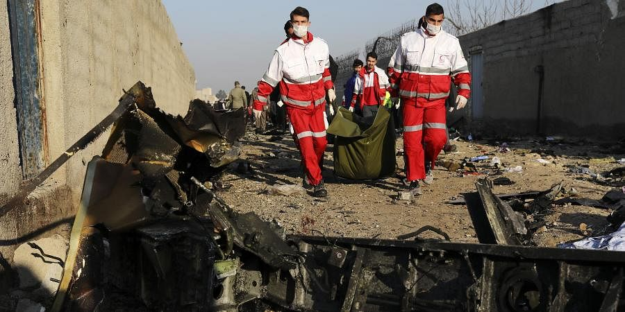 Rescue workers carry the body of a victim of an Ukrainian plane crash among debris of the plane in Shahedshahr, southwest of the capital Tehran, Iran. (Photo   AP)