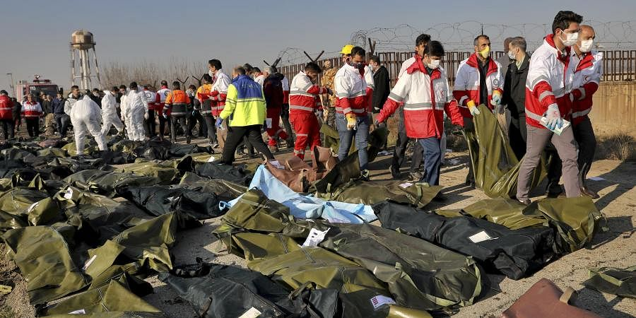 Rescue workers recover bodies of victims at the scene where a Ukrainian plane crashed in Shahedshahr, southwest of Tehran. (Photo | AP)
