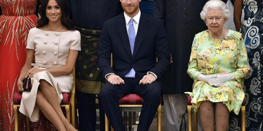 Britain's Queen Elizabeth, Prince Harry and Meghan, Duchess of Sussex pose for a group photo at the Queen's Young Leaders Awards Ceremony at Buckingham Palace in London