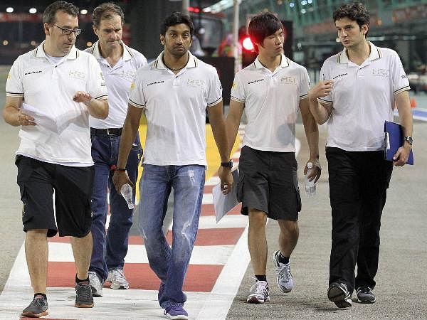 Hispania Racing Team Formula One driver Narain Karthikeyan, centre, of India walks with reserve driver China's Ma Ma Qinghua, second right, as inspect the Marina Bay City Circuit at the Singapore Formula One Grand Prix in Singapore.