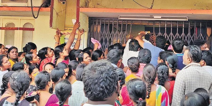 Women queue up at a bank in Krishna Lanka in Vijayawada on Monday,  to withdraw financial aid under Amma Vodi scheme