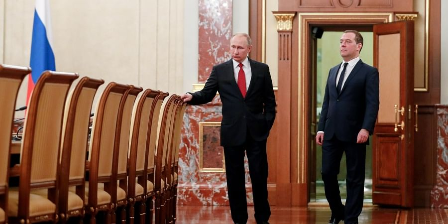 Russian President Vladimir Putin, right, and Russian Prime Minister Dmitry Medvedev talk to each other prior to a cabinet meeting in Moscow, Russia. (Photo | AP)