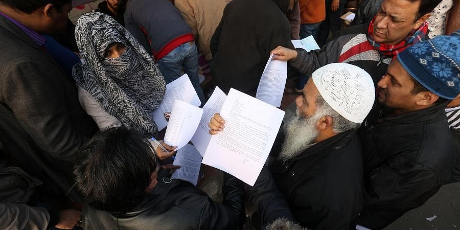 Protesters invite people to sign a letter addressing President Ram Nath Kovind and Chief Justice of India Sharad Arvind Bobde regarding abrogation of the CAA at Shaheen Bagh on Tuesday