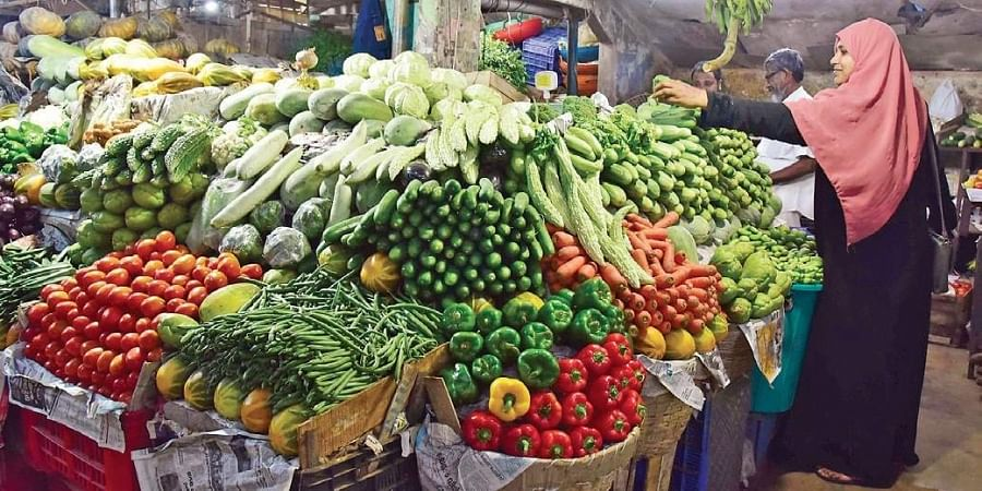 A woman buying vegetables from a shop.