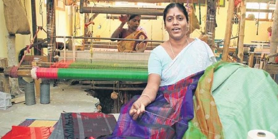 A weaver displays sarees made of beach wood and banana fibre.