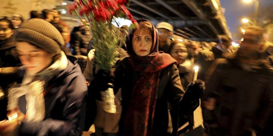 People gather for a candlelight vigil to remember the victims of the Ukraine plane crash, at the gate of Amri Kabir University that some of the victims of the crash were former students of, in Tehran, Iran.