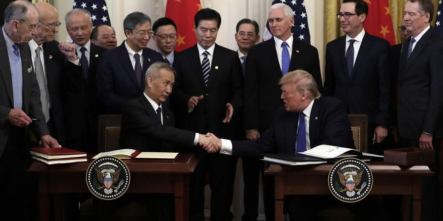 President Donald Trump shakes hands with Chinese Vice Premier Liu He, after signing a trade agreement in the East Room of the White House. (Photo | AP)