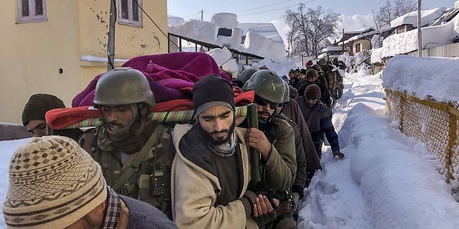 Chinar Corps personnel carry an expecting mother Shamima who required an emergency help to hospital through heavy snow. (Photo | PTI)