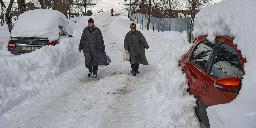 Men walk on a snow-covered road after heavy snowfall at Ferozpora village of Tangmarg in Baramulla district of north Kashmir Wednesday Jan. 15 2020. (Photo | PTI)