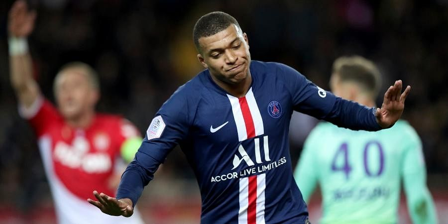 PSG's Kylian Mbappe celebrates after scoring his side's opening goal during the French League One soccer match between Monaco and Paris Saint-Germain at the Louis II stadium in Monaco.