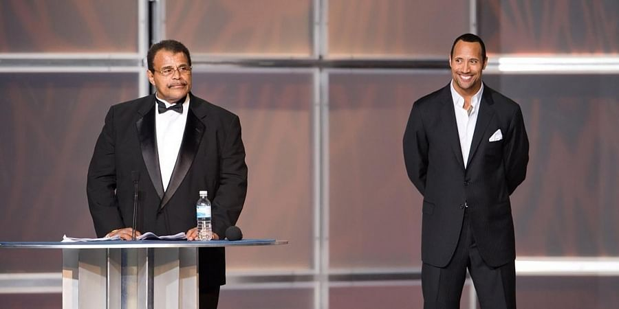 """Rocky 'Soul Man' Johnson, left, speaks at his WWE Hall of Fame induction ceremony, as his son, Dwayne """"The Rock"""" Johnson watches."""