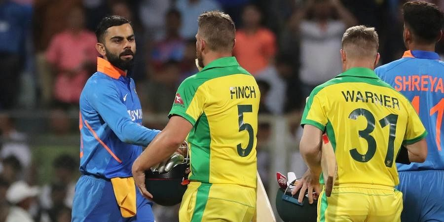 Australia's captain Aaron Finch, second from right, is congratulated by Indian captain Virat Kohli, left, after Australia won the first ODI match between India and Australia in Mumbai.