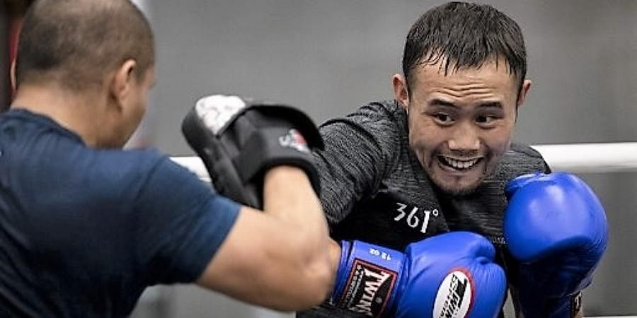 Chinese boxer and food delivery man Zhang Fangyong htting the mits during a practice at a boxing gym in Beijing.