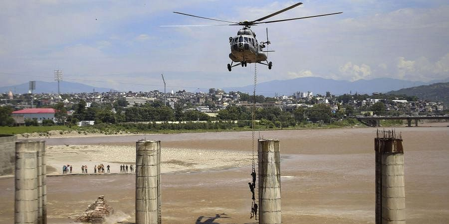 A chopper of the Indian Air Force approaches to airlift two persons stuck on an under-construction bridge on the flooded Tawi River in Jammu Monday August 19 2019.