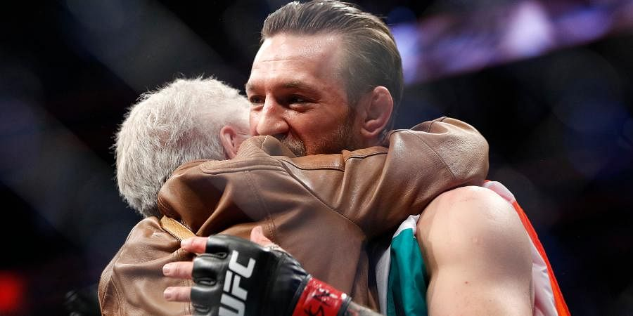 Conor McGregor, right, embraces Jerry Cerrone, the grandmother of Donald 'Cowboy' Cerrone, after a UFC 246 welterweight mixed martial arts bout.
