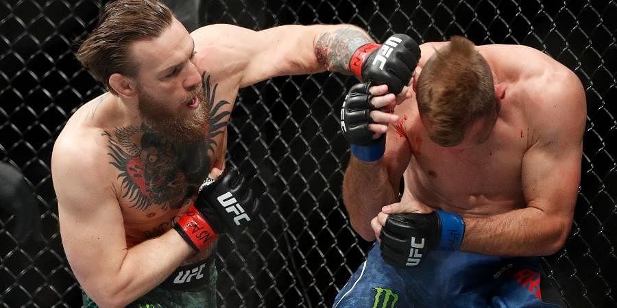 Conor McGregor kicks Donald 'Cowboy' Cerrone during a UFC 246 welterweight mixed martial arts bout.
