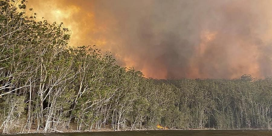Smoke and wildfire rage behind Lake Conjola, Australia, Thursday, Jan. 2, 2020.