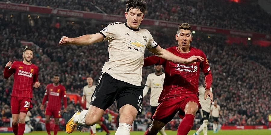 Manchester United's Harry Maguire and Liverpool's Roberto Firmino, right, challenge for the ball during the English Premier League soccer match between Liverpool and Manchester United at Anfield Stadium in Liverpool.