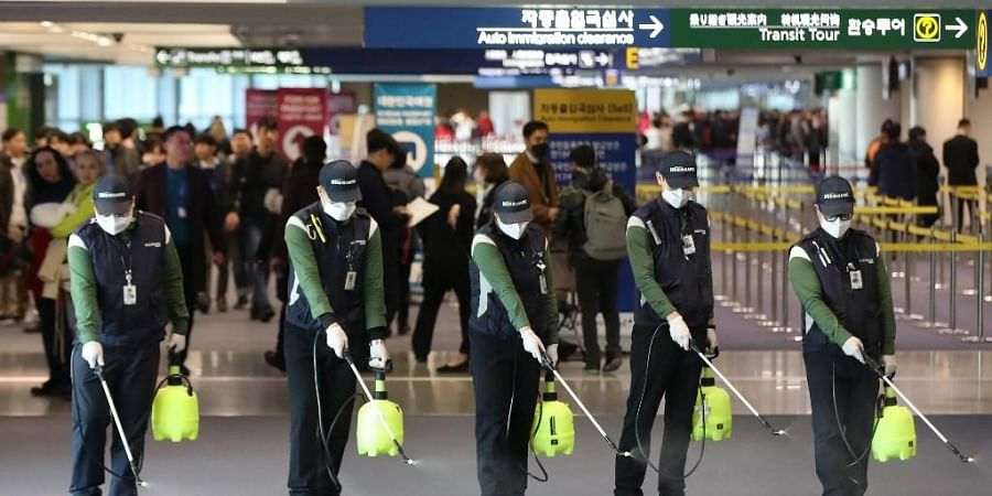 Workers from a cleaning service spray disinfectant at the customs, immigration and quarantine (CIQ) area at Incheon international airport, west of Seoul, on January 21, 2020. South Korea on January 20 confirmed its first case of the SARS-like virus that is spreading in China, as concerns mount about a wider outbreak.