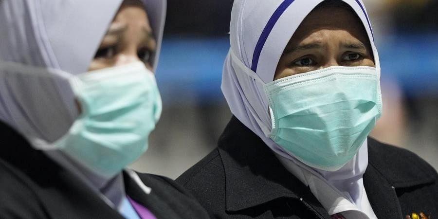 Health officials wear face masks at an inspection site at the Kuala Lumpur International Airport in Sepang, Malaysia