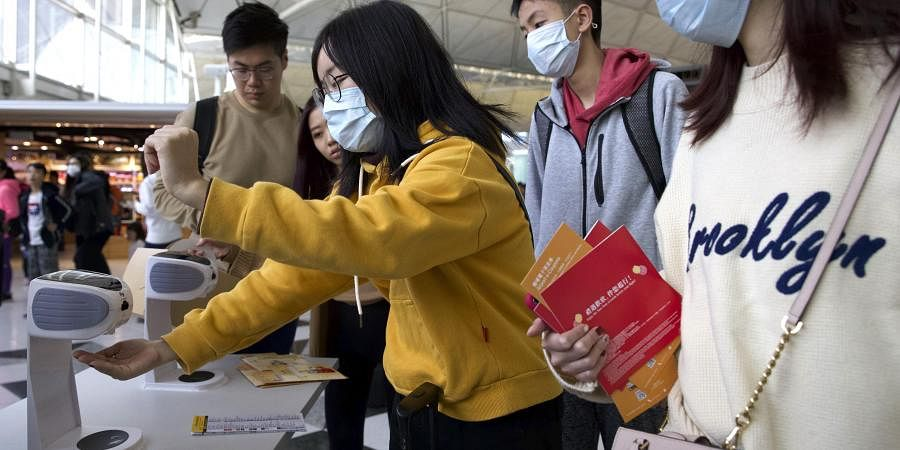Travelers wearing face masks gather at Hong Kong International Airport in Hong Kong.