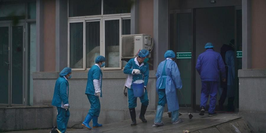Hospital staff wash the emergency entrance of Wuhan Medical Treatment Center, where some infected with a new virus are being treated, in Wuhan, China, Wednesday, January 22, 2020.