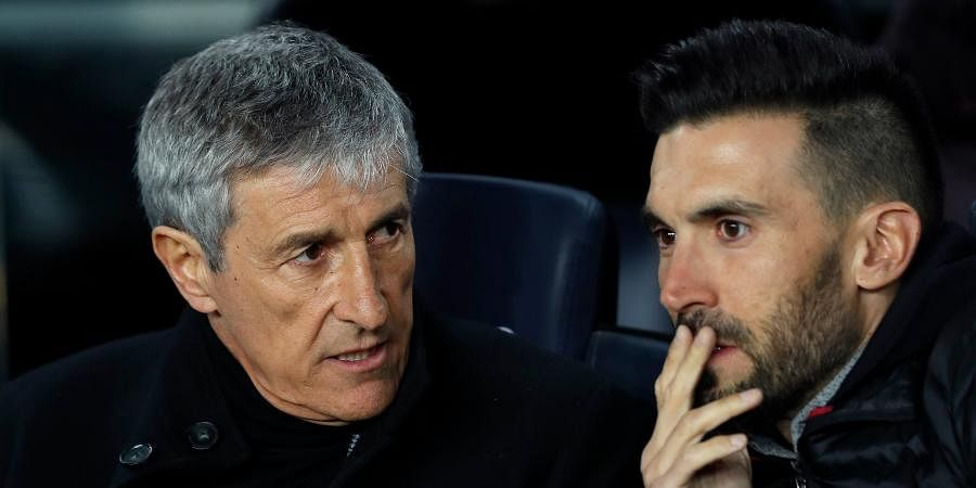 Barcelona's head coach Quique Setien talks with assistant coach Eder Sarabia, right, on the bench during a Spanish La Liga soccer match between Barcelona and Granada at Camp Nou stadium in Barcelona.