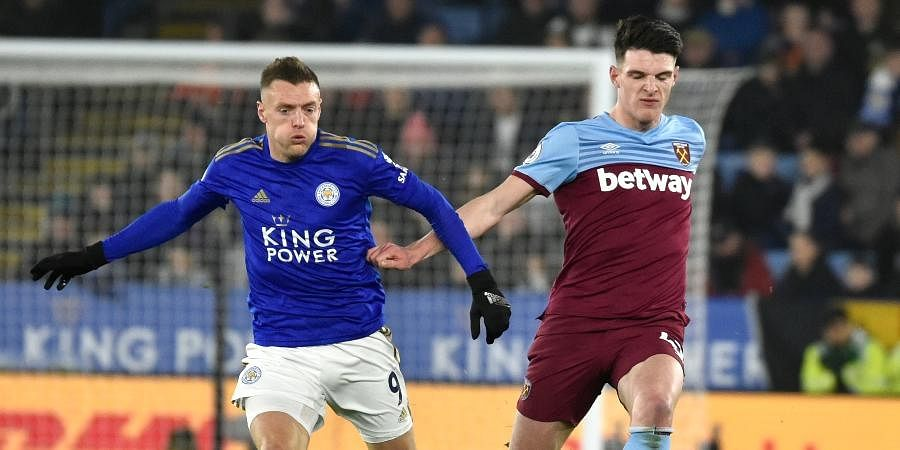 Leicester's Jamie Vardy, left, and West Ham's Declan Rice challenge for the ball during the English Premier League soccer match between Leicester City and West Ham Utd at the King Power Stadium in Leicester.